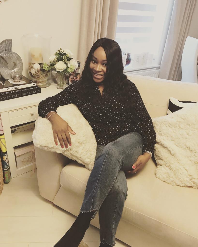 Ayesha Amato fashion blogger sitting on sofa in home